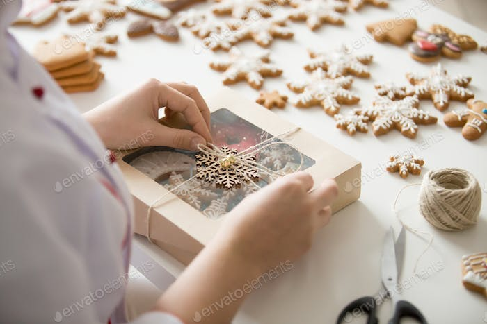 Close up of female confectioner hands wrapping a box
