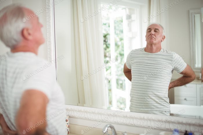 Senior man stretching in front of the mirror