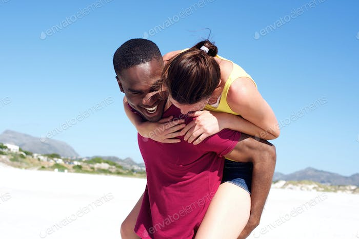Playful young couple smiling outdoors on the beach