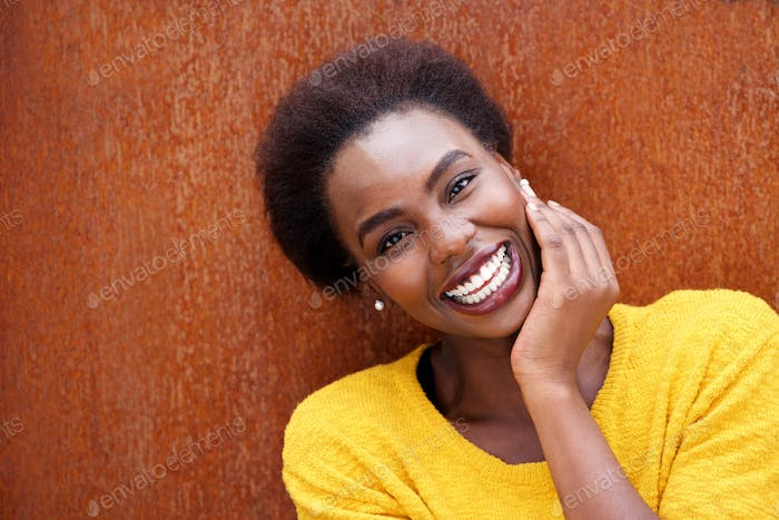Close up smiling young black woman smiling against brown background