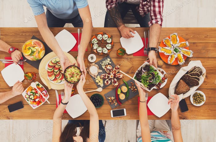 People eat healthy meals at festive table dinner party