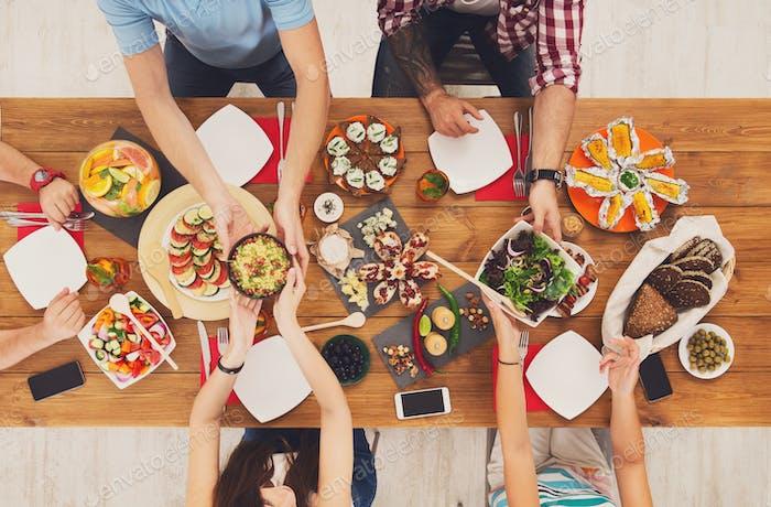 Menschen essen gesunde Mahlzeiten auf festlichen Tisch Dinnerparty