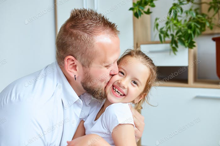 Father and daughter in white spending time at home