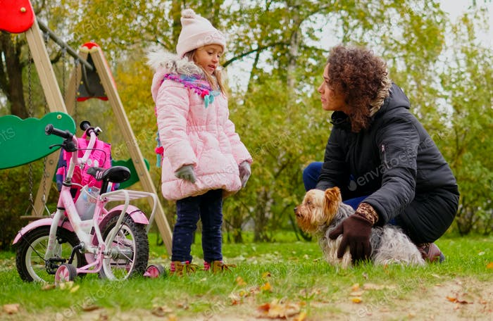 Mutter und Tochter spielen mit Hund auf Spielplatz