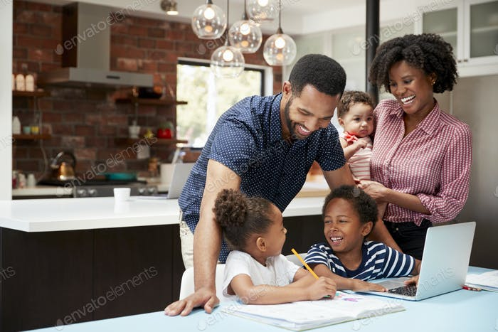 Father Helps Children With Homework Whilst Mother Holds Baby