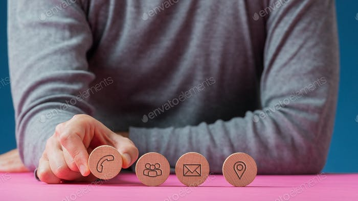 Man placing four wooden cut circles with contact and communication icons on them in a row