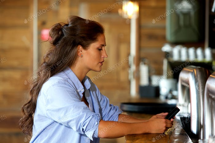 beautiful young woman using mobile at the bar