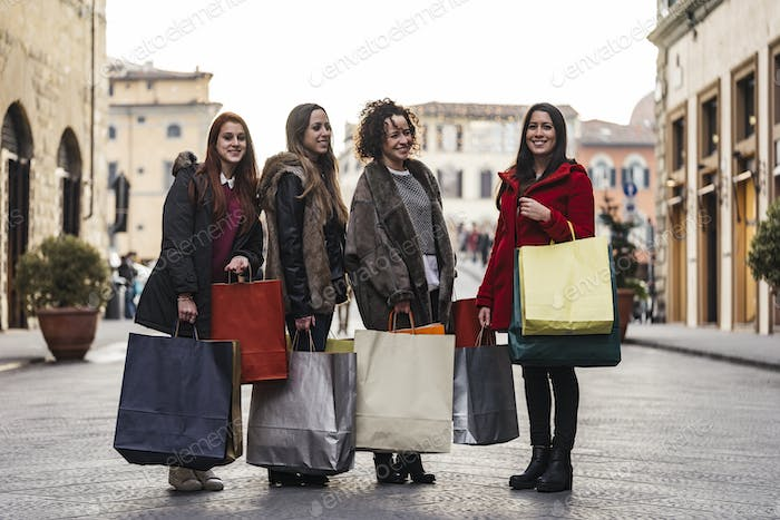 Happy female group of friends doing shopping together