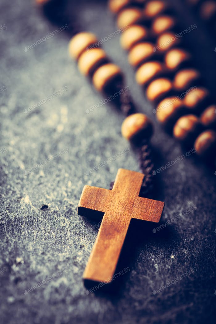 Cross and rosary on stone background.
