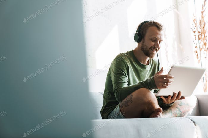 Photo of young pleased man smiling while using headphones and laptop