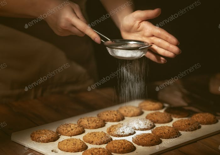 woman preparing biscuits on wooden table.