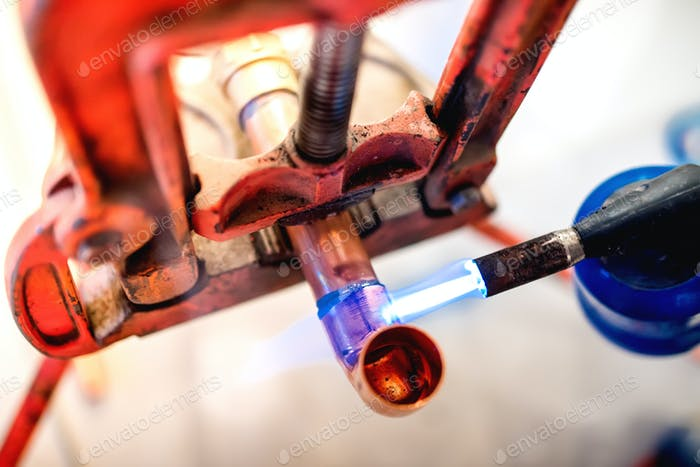industry professional plumber welding and soldering copper pipes