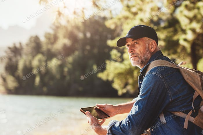 Senior man at a lake with backpack and digital tablet