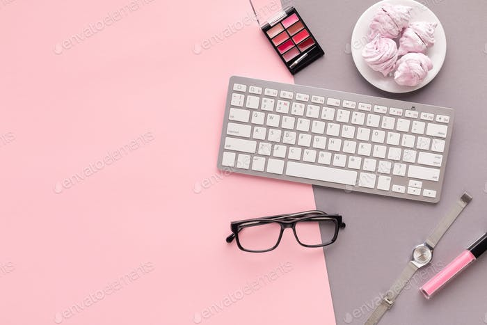 Working space with keyboard on pink background