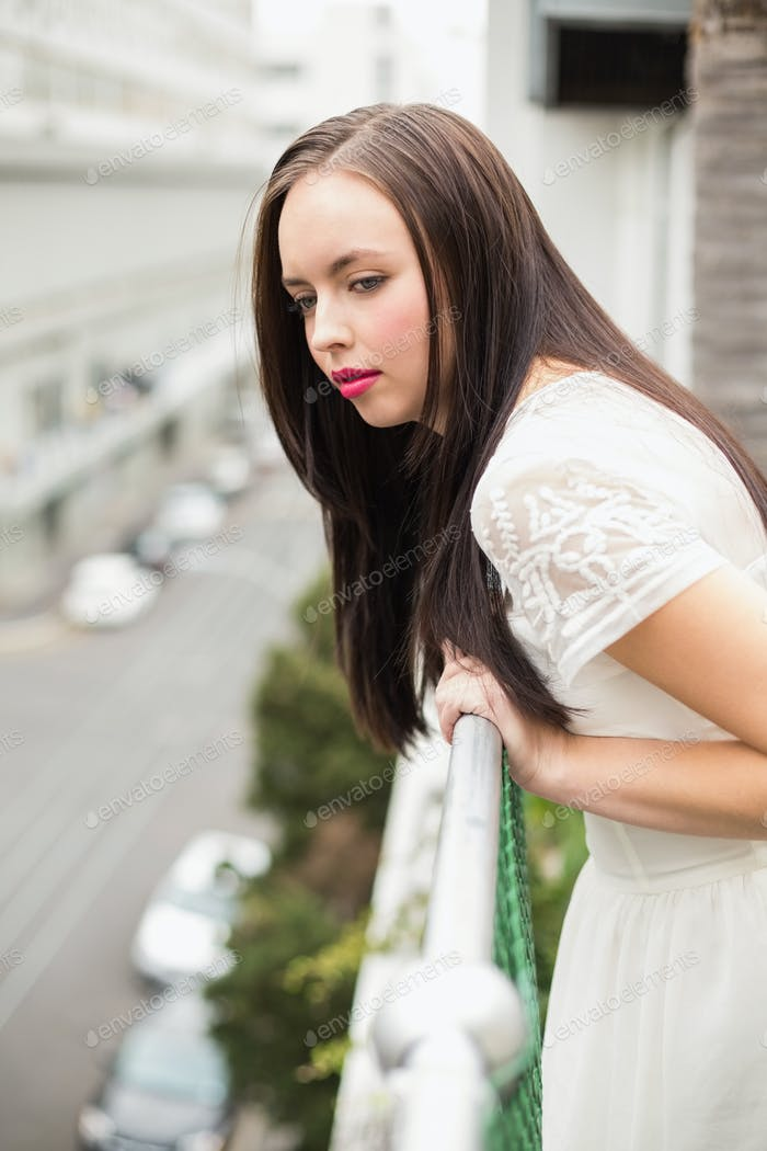 Pretty brunette looking over the balcony looking down on street