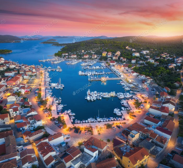 Aerial view of boats and yachts in port and city at sunset