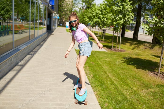 happy teenage girl in shades riding on longboard