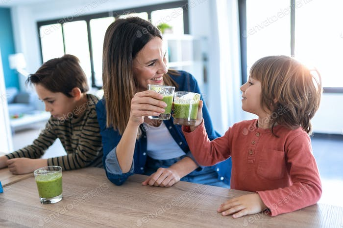 Pretty young mother with her son toasting with detox smoothie in the kitchen at home.