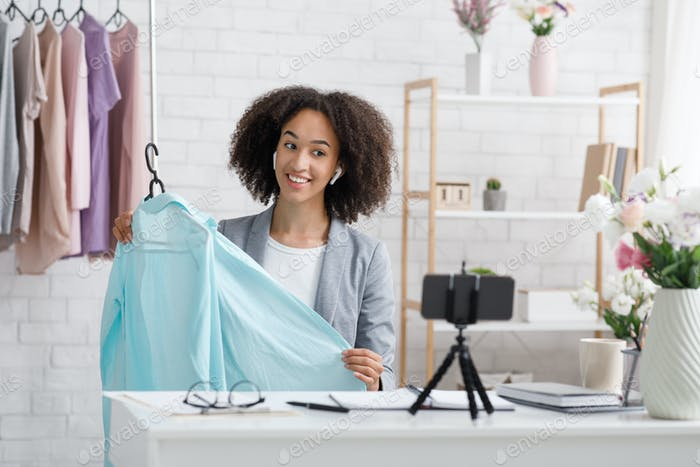 Happy african american woman in suit shows clothes and makes video about fashion