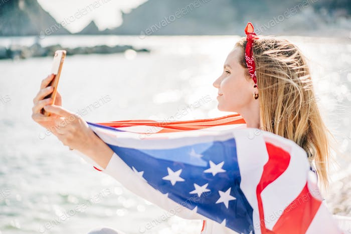 Woman with American flag on the beach. 4th of July. Independence Day.