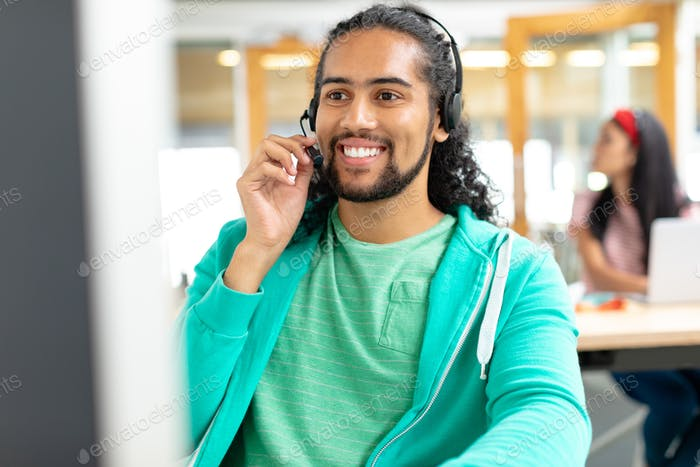 Happy African-ameican male customer service executive talking on headset in a modern office