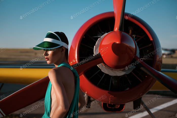 Fashion photo of a girl as a pilot in a visor next to propeller plane during sunset