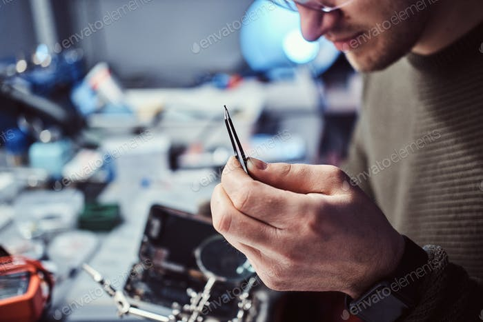 Electronic technician mending a broken phone