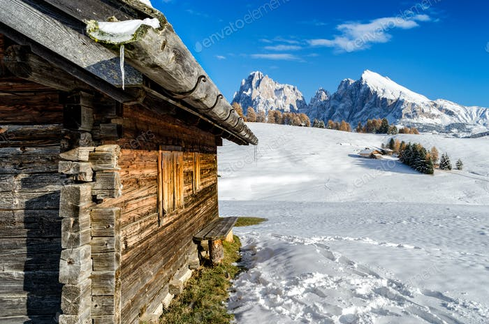 Wooden cabin in the snow with a view on the Dolomites