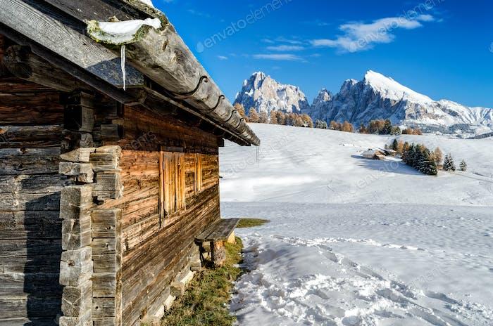 Holzhütte im Schnee mit Blick auf die Dolomiten