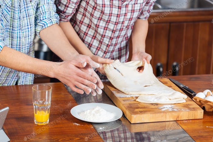 Couple standing and kneading dough on the kitchen