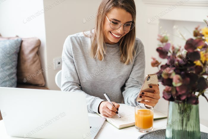 Photo of cheerful woman making notes in planner while using cellphone