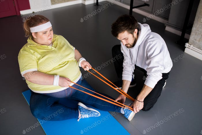 Fat Woman Stretching in Fitness Class