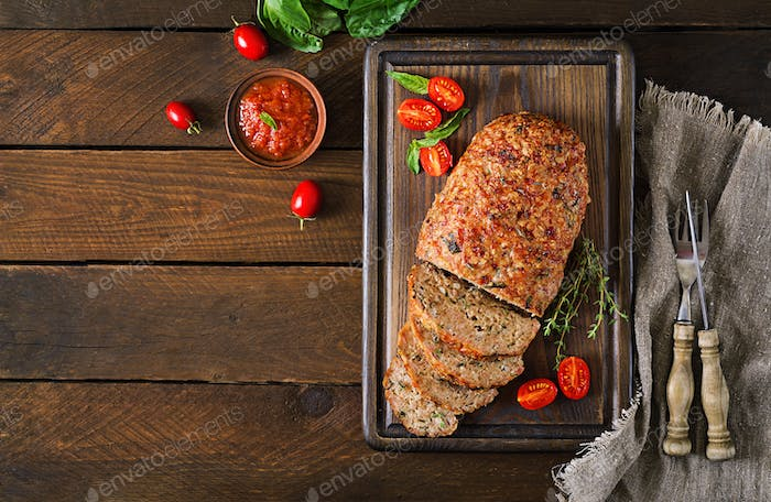 Tasty homemade ground  baked turkey meatloaf on wooden table.