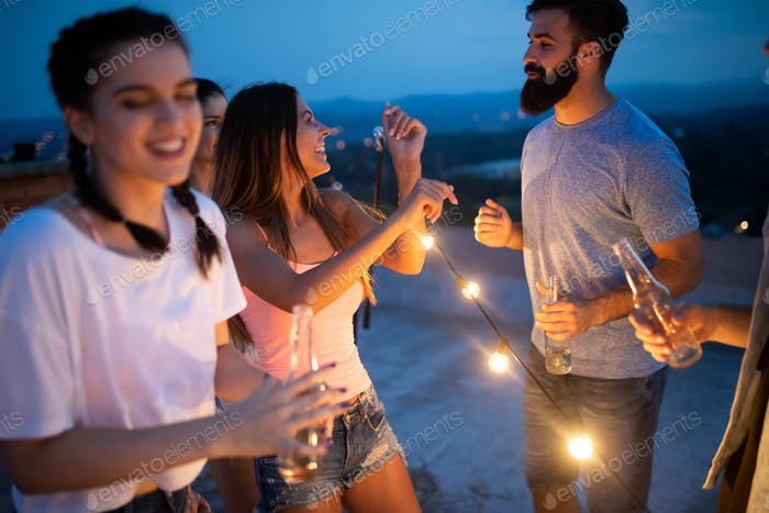 Carefree group of happy friends enjoying party on rooftop terrace