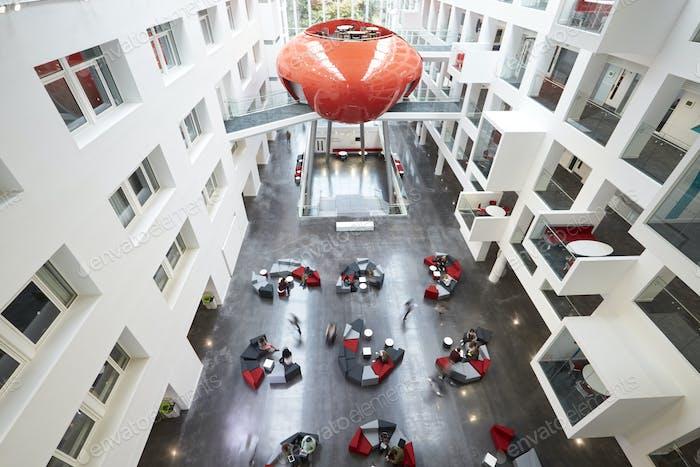 Students moving around the atrium area of modern university