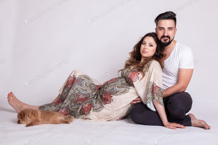 Gorgeous pregnant woman with her husband in studio photo