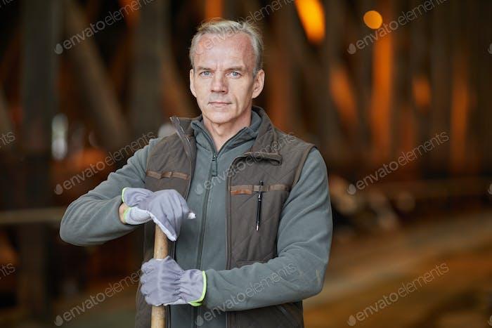 Mature Man Holding Shovel at Farm