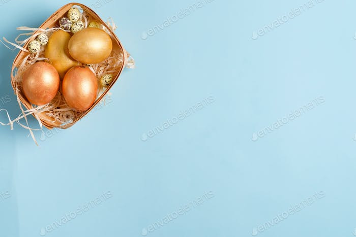 Beautiful Easter golden color eggs on blue background, copy space