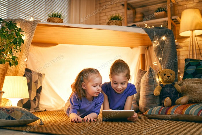 children are playing with tablet in tent