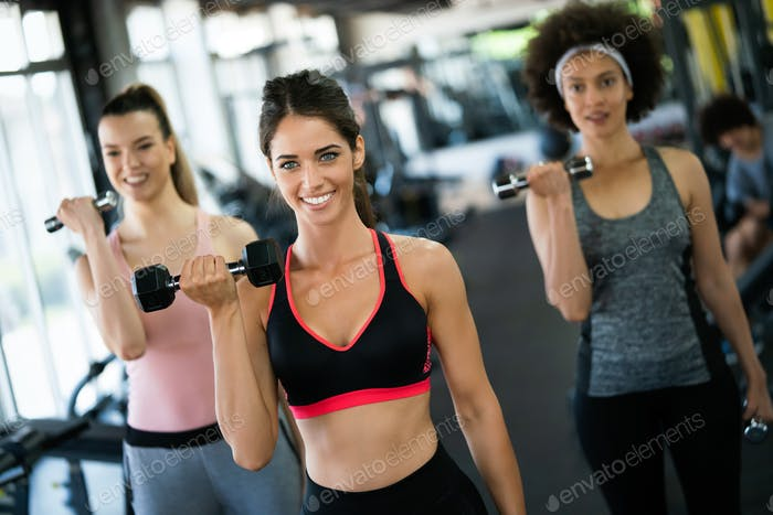 Diversity group of people training in a gym. Trainer and sportive persons exercising
