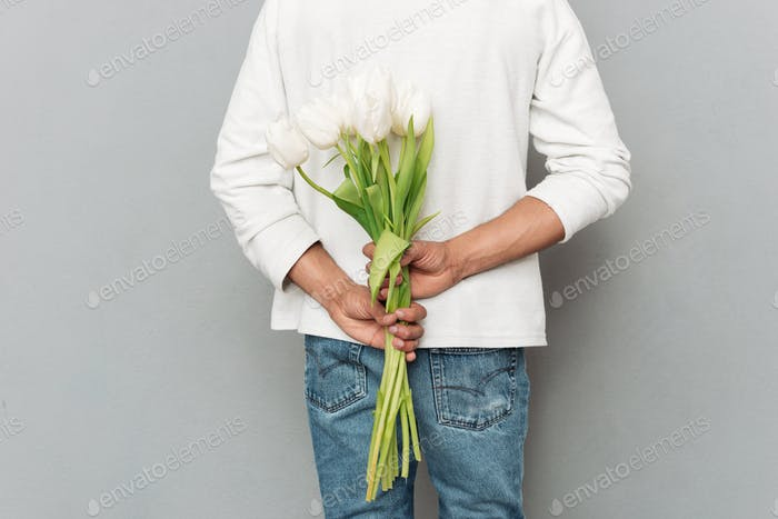 Cropped back view photo of young man with flowers.