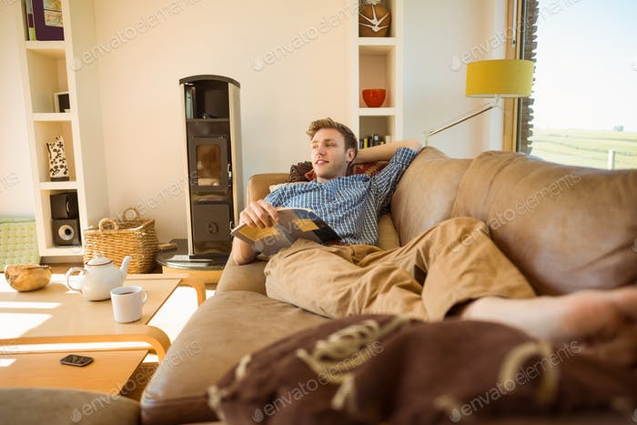Young man reading on his couch at home in the living room