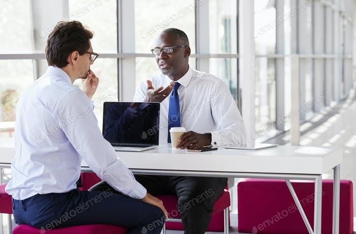 Two businessmen talk during a business meeting