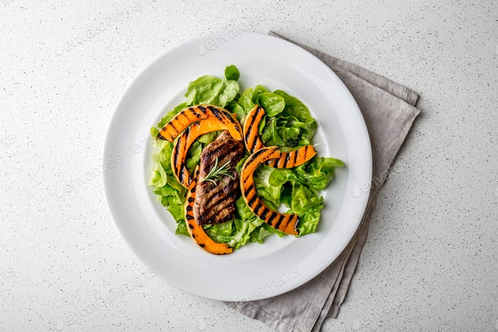 Grilled pumpkin and lettuce salad. Top view, white background