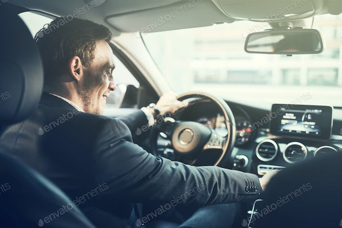 Smiling young businessman changing music stations while driving