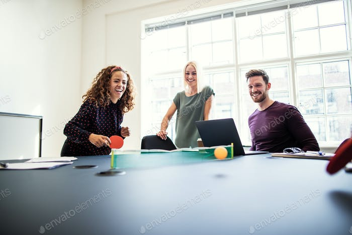 Laughing office colleagues playing table tennis during a work break