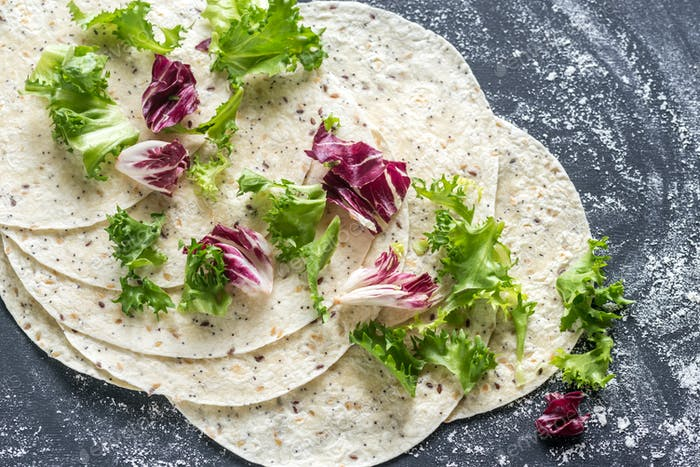 Tortillas with lettuce on a black surface