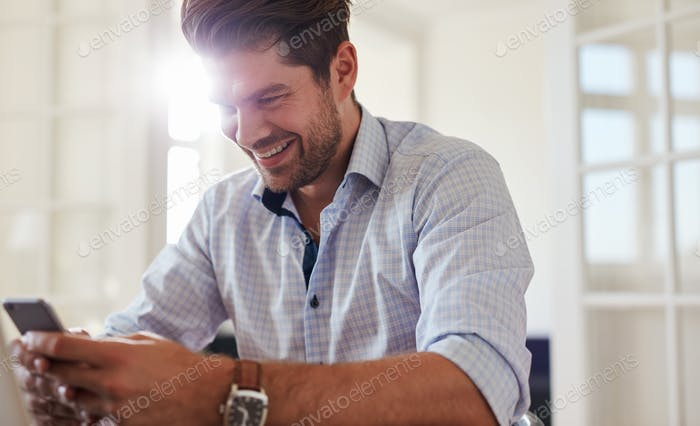 Happy young man using mobile phone at home