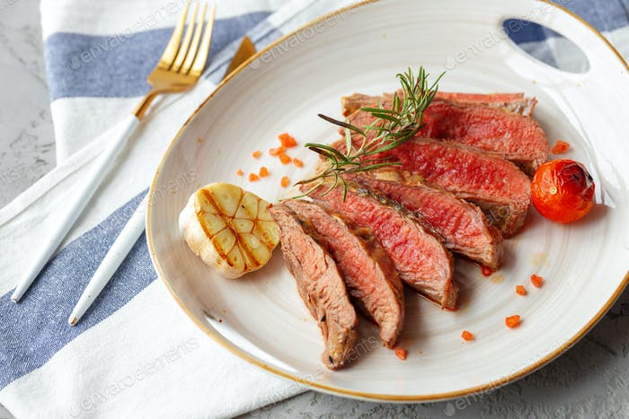 Mittelseltenes gegrilltes Steak in Scheiben geschnitten auf Teller