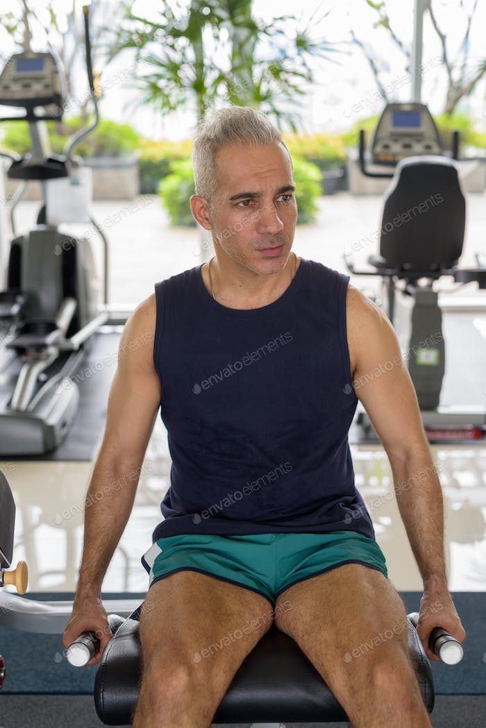 Mature handsome Persian man doing leg extension exercise